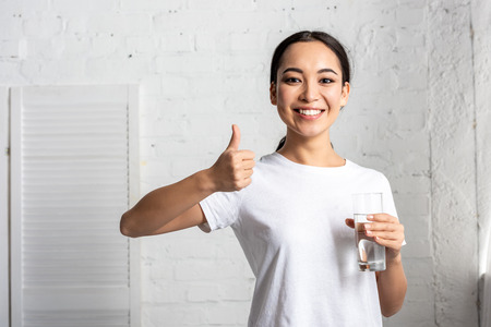 smiling young asian woman in white t-shirt holding glass of water and showing thumb up Фото со стока