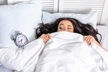 Young beautiful asian woman looking at alarm clock from under the blanket with squinting one eye Stockfoto