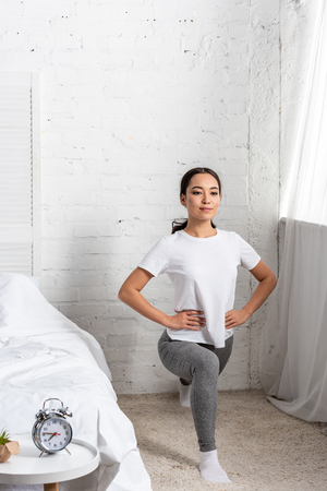 asian woman in white t-shirt and grey leggings doing lunges exercises