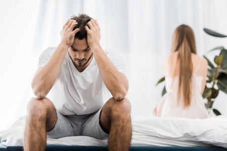 depressed man with hands on head having sexual problems while sitting on bed with girlfriend Stock Photo