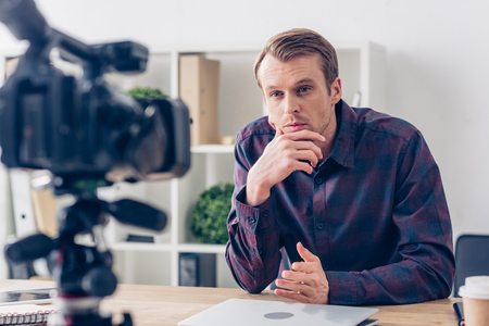 handsome pensive male video blogger recording vlog in office Stock Photo