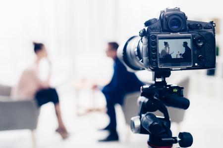 Empresario dando entrevista al periodista en la oficina, cámara sobre trípode en primer plano Foto de archivo