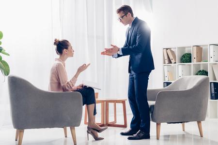 Hombre de negocios irritado de pie y gesticulando mientras da una entrevista al periodista en la oficina