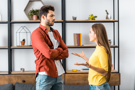 angry boyfriend standing with crossed arms while girlfriend quarreling in living room
