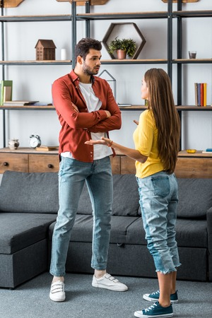 boyfriend and girlfriend standing and arguing in living room