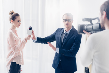 handsome businessman in suit rejecting giving video interview to journalist and gesturing in office Foto de archivo - 118056232