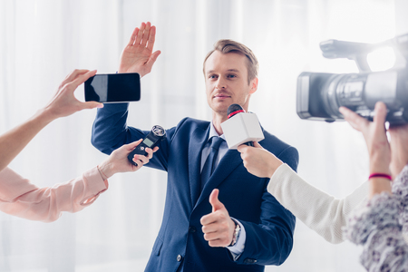 handsome businessman giving interview to journalists in office, waving hand and showing thumb up