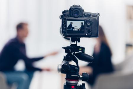 donna d'affari in tuta che dà un'intervista al giornalista in ufficio, fotocamera in primo piano