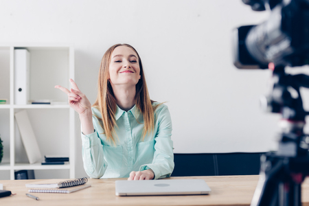 smiling attractive female video blogger recording vlog and showing two fingers in office