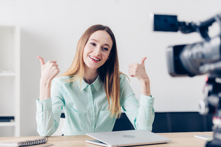 smiling attractive female video blogger recording vlog and showing thumbs up in office Stock Photo