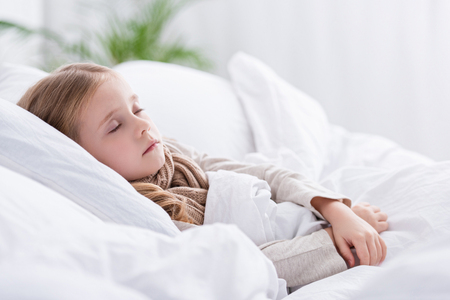 sick child with scarf over neck sleeping in bed at home