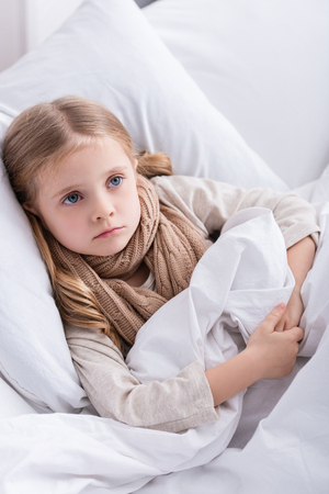 sick child with scarf over neck lying in bed at home and looking away Фото со стока