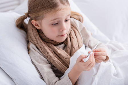 surprised sick child with scarf over neck lying in bed and checking temperature with thermometer at home