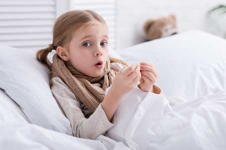shocked sick kid with scarf over neck lying in bed and checking temperature with thermometer at home