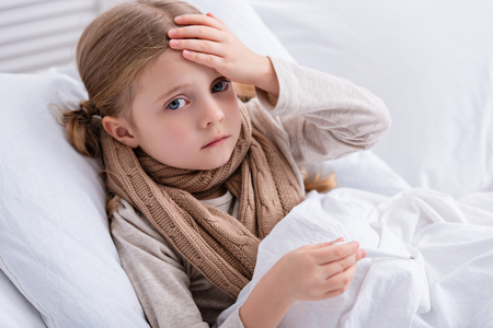 sick child with scarf over neck lying in bed, holding thermometer and touching forehead at home
