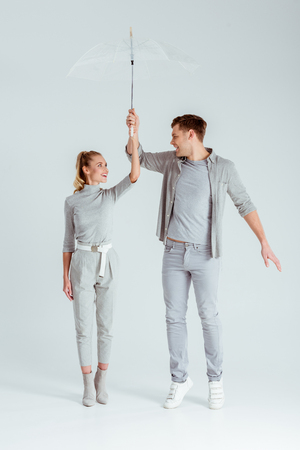 happy couple looking at each other, standing on tiptoe and posing with transparent umbrella on grey background