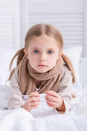 sick child with scarf over neck lying in bed, holding thermometer and looking at camera at home