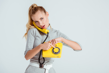 beautiful woman dialing phone number on vintage yellow telephone isolated on grey
