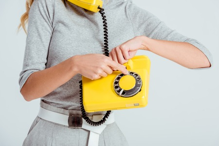 cropped view of woman dialing phone number on vintage yellow telephone isolated on grey
