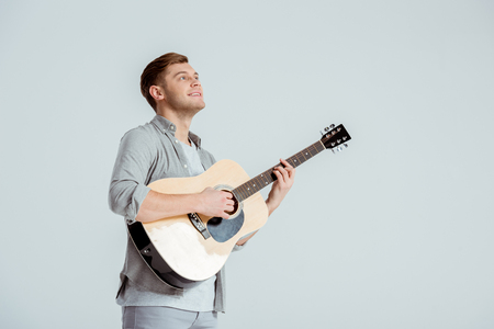 smiling man in grey clothing playing acoustic guitar isolated on grey