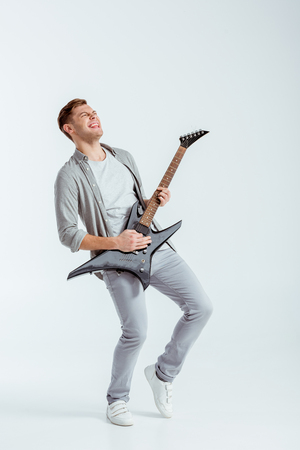 excited man in grey clothing playing electric guitar on grey background