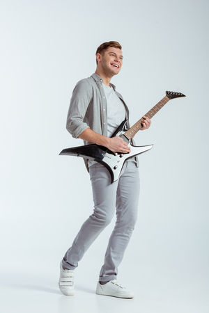 excited smiling man in grey clothing playing electric guitar on grey background