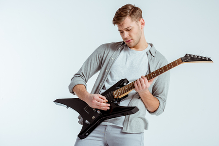 handsome focused man in grey clothing playing electric guitar isolated on grey