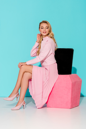 beautiful woman in pink dress sitting on big nail polish model and posing on turquoise background