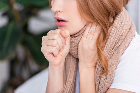 cropped image of sick woman coughing and touching neck at home