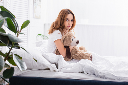 side view of sick woman with scarf sitting on bed and hugging teddy bear at home, looking at camera 스톡 콘텐츠