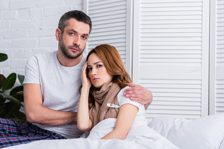 handsome husband hugging sick wife in bedroom and they looking at camera Stock Photo