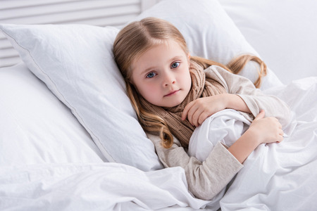 sick child with scarf over neck lying in bed at home and looking at camera