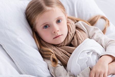 portrait of sick child with scarf over neck lying in bed at home and looking at camera Фото со стока