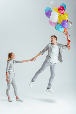 woman in grey clothing holding hand of happy man jumping in air with bundle of colorful balloons on grey background Stok Fotoğraf
