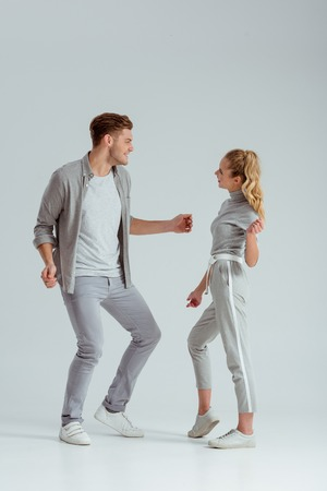 beautiful couple in grey clothing looking at each other and dancing isolated on grey