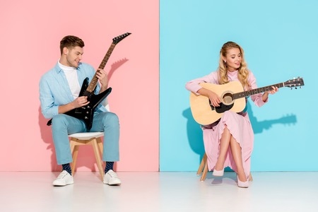 beautiful couple playing electric and acoustic guitars on pink and blue background