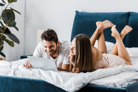young smiling couple lying in bed with crossed legs and using laptop Stock Photo