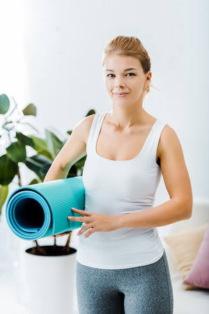 attractive woman in sportswear holding fitness mat and looking at camera in living room