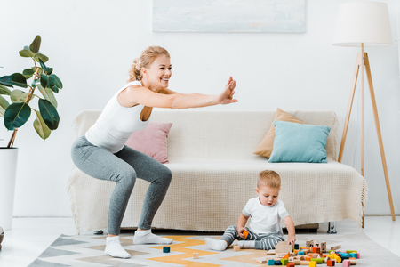 attractive mother doing squats and cute toddler son sitting on carpet and playing with multicolored cubes at home Stock Photo
