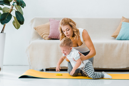 attractive woman holding crying toddler boy on fitness mat in living room Banco de Imagens