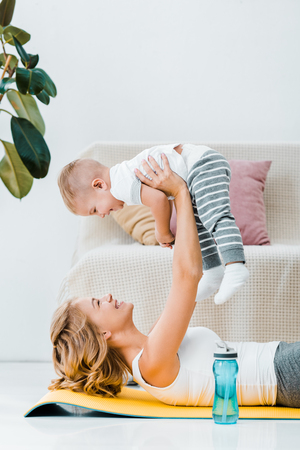 woman lying near plant and raising adorable child above head