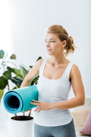 attractive woman in sportswear holding fitness mat in living room