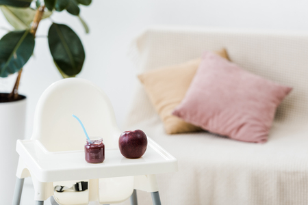 red apple and baby food jar with spoon on highchair in living room