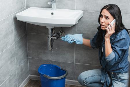 Shocked woman talking on smartphone while repairing pipe in bathroom