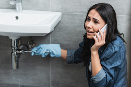 Stressed girl repairing pipe with wrench and talking on smartphone