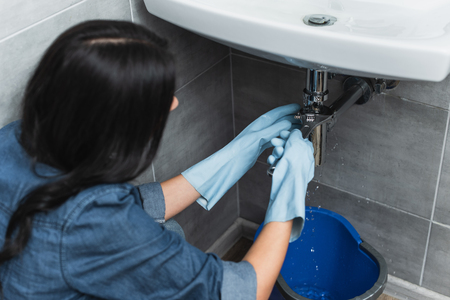 Brunette woman in rubber gloves repairing pipe with wrench Imagens