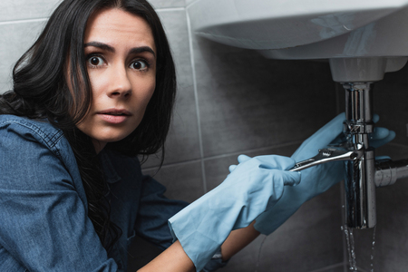 Amazed brunette woman in rubber gloves repairing sink pipe with wrench