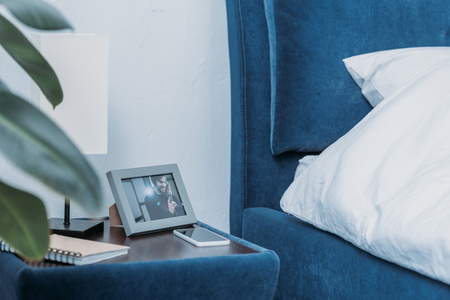 selective focus of photo frame with picture of man, notebook and smartphone on bedside table