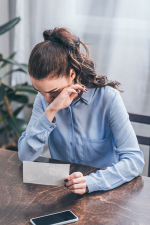 upset woman in blue blouse sitting at table with photo, smartphone and crying at home, grieving disorder concept