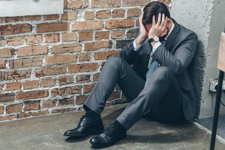 sad man in grey suit sitting in corner on floor and crying on textured background in room, grieving disorder concept